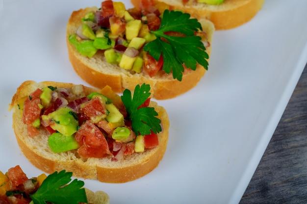 Sandwich mit avocado und lachs auf frühlingszwiebeln, brot und tomaten.