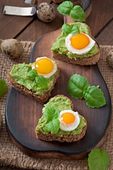 Sandwich mit avocadopaste und ei in form des herzens