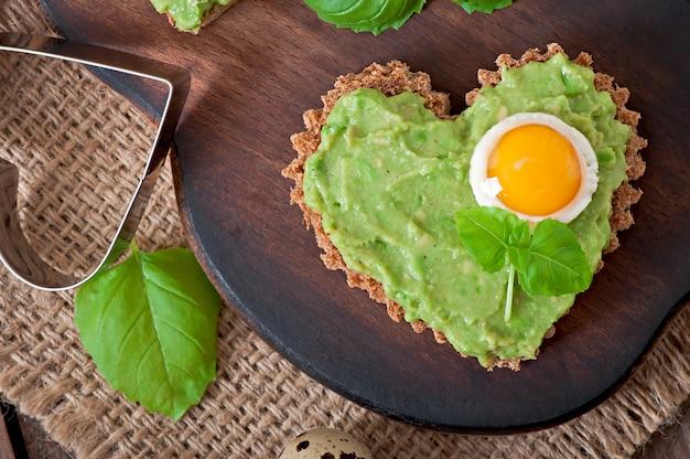 Sandwich mit avocadopaste und ei in form eines herzens