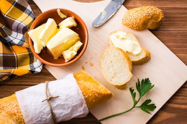 Sandwich mit butter und geschnittenem stangenbrot auf einem schneidebrett. ansicht von oben