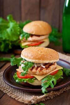 Sandwich mit chicken burger, tomaten, käse und salat