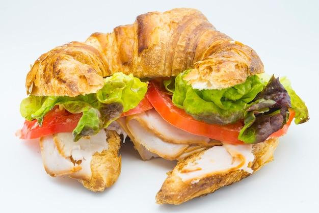 Sandwich mit croissant aus salat, tomate und geräuchertem truthahn