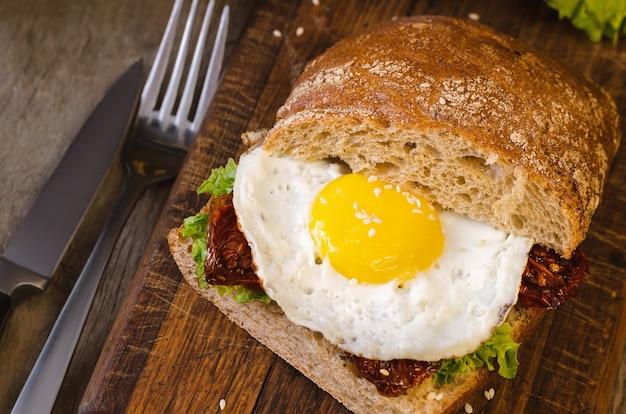 Sandwich mit dunklem brot, getrockneten tomaten und ei.