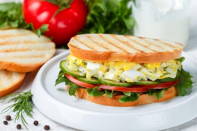Sandwich mit eiersalat, kopfsalat, tomaten, gurken und dill, feinschmeckerisches frühstück