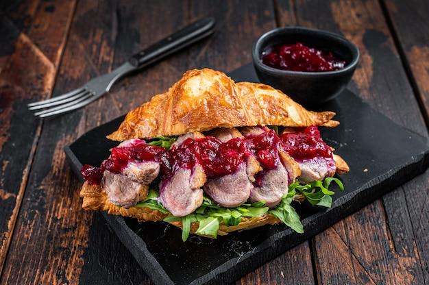 Sandwich mit entenbrustfiletsteakscheiben, rucola und sauce. dunkler holztisch. draufsicht.