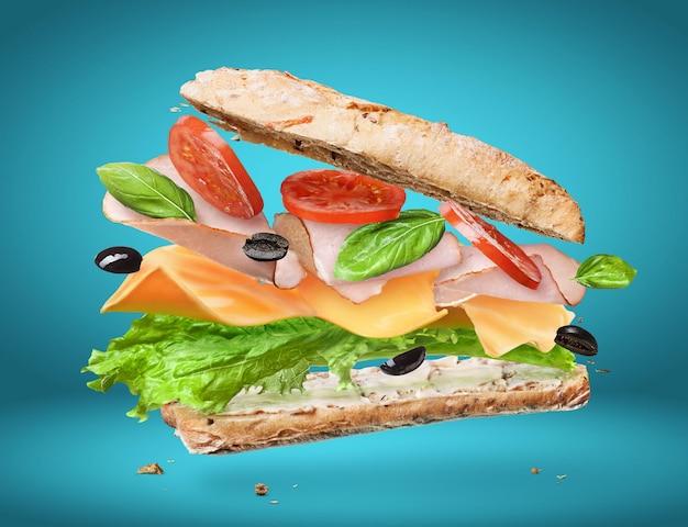 Sandwich mit fallenden zutaten in der luft isoliert auf blauer oberfläche
