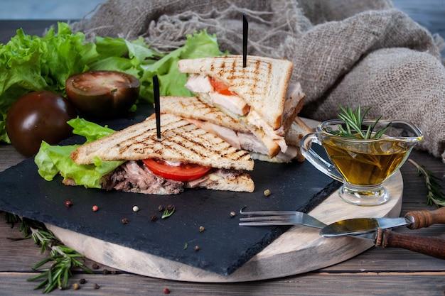 Sandwich mit fleisch und frischgemüse auf einem holztisch