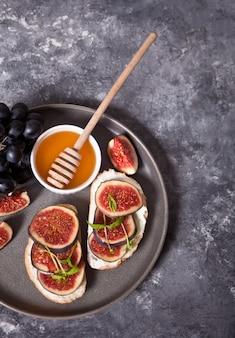 Sandwich mit frischkäse, feigen und honig diente auf der grauen platte auf dem beton. gesundes essen .