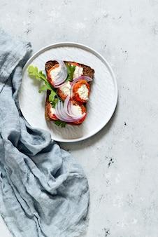 Sandwich mit gebackenem, mit pfeffer gefülltem frischkäse, rucola, geräuchertem paprika und blauen zwiebeln an einer blauen wand. italienische bruschetta antipasti. vegetarisches essen.