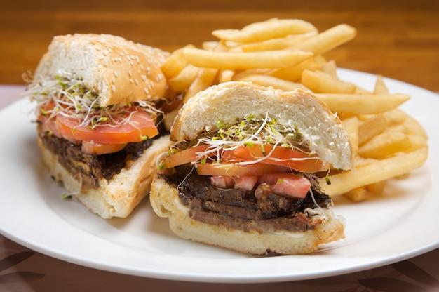 Sandwich mit gegrilltem kalbfleisch mit soße und tomate. begleitet von pommes frites
