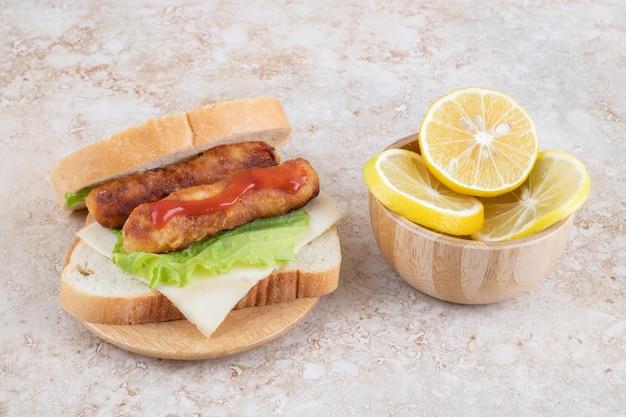 Sandwich mit gegrillten würstchen, frischkäse und kräutern.