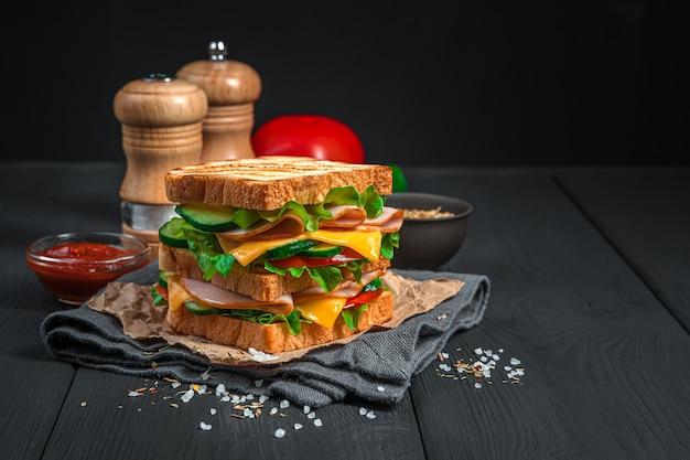 Sandwich mit gemüse und schinken auf dem hintergrund der gewürzsauce. seitenansicht, textfreiraum