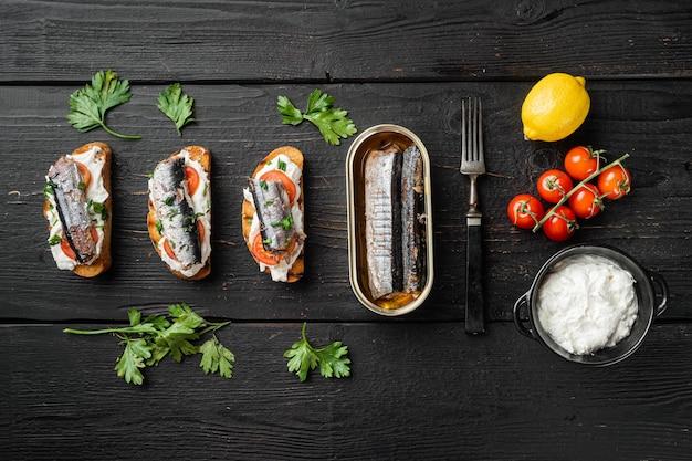 Sandwich mit geräuchertem fisch, auf schwarzem holztischhintergrund, draufsicht flach