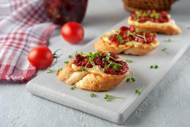 Sandwich mit hausgemachter mayonnaise, sonnengetrockneten tomaten und mikrogemüse, serviert auf einem brett auf grauer oberfläche
