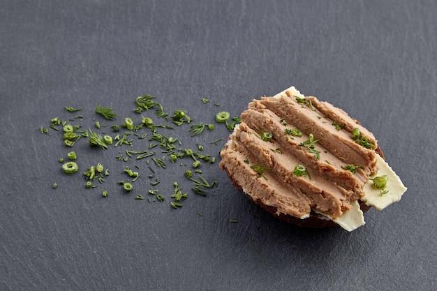 Sandwich mit hausgemachter pastete auf brot und butter, garniert mit dill auf einem schwarzen schieferbrett