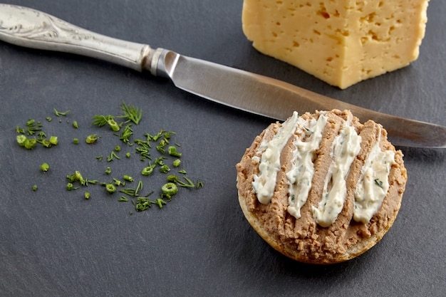 Sandwich mit hausgemachter pastete auf brot und butter und messer, garniert mit dill auf einem schwarzen schieferbrett
