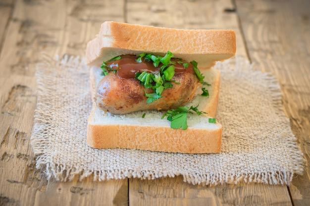 Sandwich mit hausgemachter wurst, gewürzen und soße.