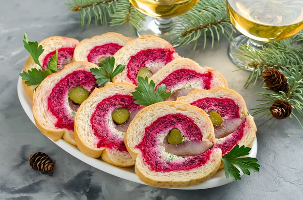 Sandwich mit heringsfilet, zwiebel, eingelegter gurke, frischkäse und roter beete. feiertags-aperitif