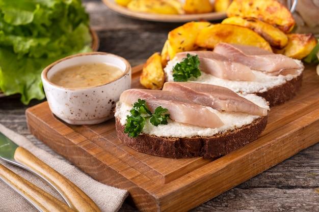 Sandwich mit heringsfilets und ofenkartoffel in einem holzbrett.