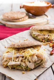 Sandwich mit hühnchen und guacamole, käse.