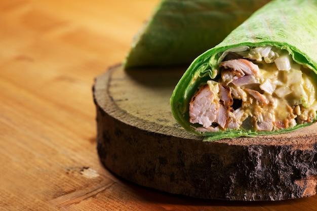 Sandwich mit hühner- und gemüsenahaufnahme. fastfood auf der straße