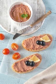 Sandwich mit hühnerleberpastete und schwarzen oliven