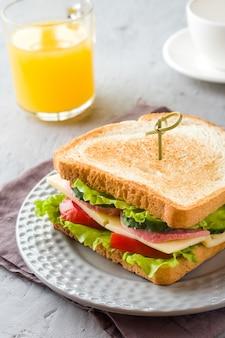 Sandwich mit käse, schinken und frischem gemüse auf einem teller.
