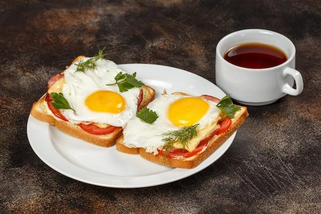 Sandwich mit käse, speck, tomate und spiegelei auf teller, tasse tee