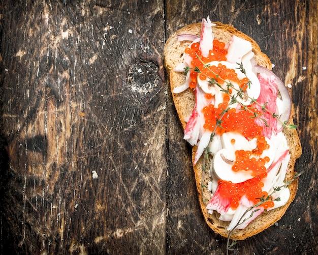Sandwich mit krabbenfleisch, pilzen und rotem kaviar auf holztisch.