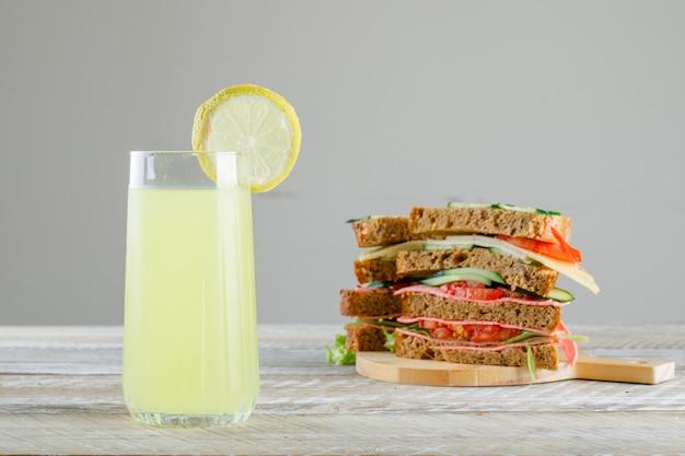 Sandwich mit limonade, schneidebrett seitenansicht auf grauem und holztisch