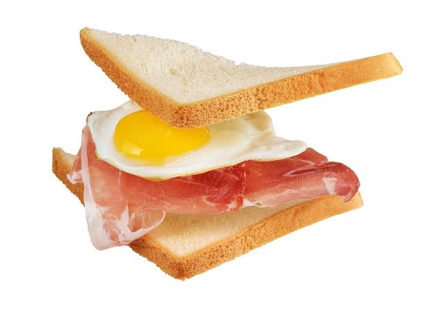 Sandwich mit mit fliegenden zutaten, spiegelei, speck, brot