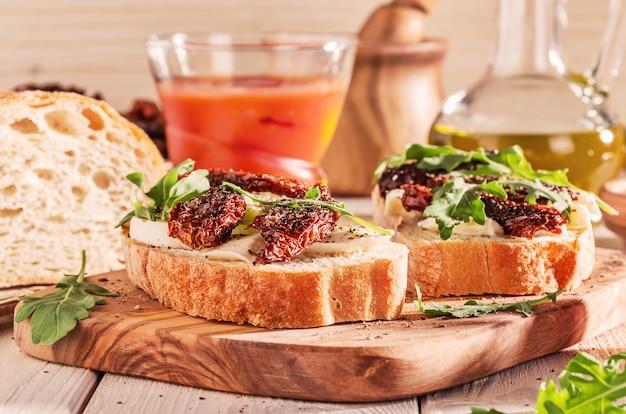 Sandwich mit mozzarella, sonnengetrockneten tomaten und rucola.