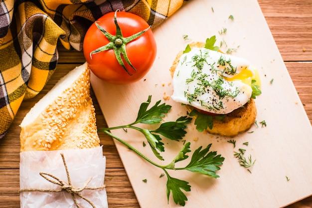 Sandwich mit pochiertem ei, tomate, stangenbrot und petersilie auf einem schneidebrett. ansicht von oben