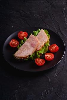 Sandwich mit putenschinkenfleisch, grünem salat und frischen kirschtomatenscheiben auf schwarzem teller