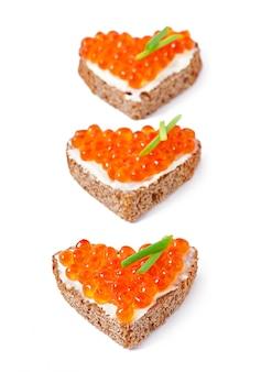 Sandwich mit rotem kaviar in form eines herzens