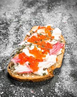 Sandwich mit rotem kaviar, krabbenfleisch und frischen pilzen. auf einem rustikalen hintergrund.