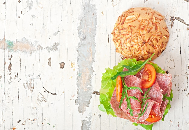 Sandwich mit salami, salat, tomate und rucola