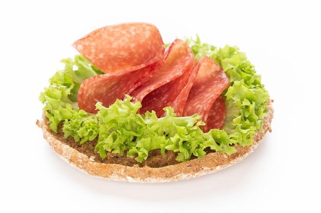 Sandwich mit salami-wurst auf weißer oberfläche.