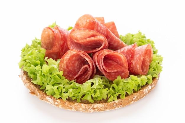 Sandwich mit salamiwurst auf weißem hintergrund.