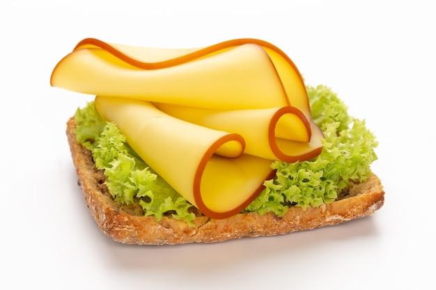 Sandwich mit salat, käse auf weißem hintergrund.