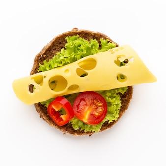 Sandwich mit salat, käse auf weißem tisch.
