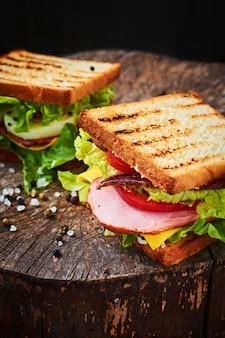 Sandwich mit salat, schinken, tomaten und zwiebeln auf dunklem hintergrund