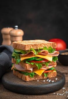 Sandwich mit schinken, käse, tomaten und gurken auf braunem hintergrund. seitenansicht, nahaufnahme