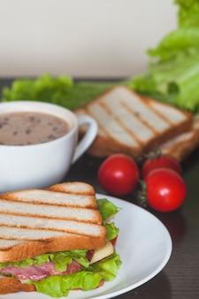 Sandwich mit schinken; spinatblatt und -käse auf weißer platte mit kaffee