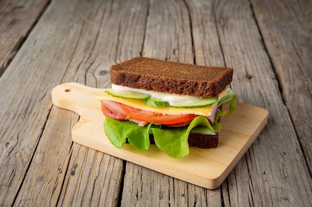 Sandwich mit schwarzbrot, schinken, käse, tomaten, gurken, salat