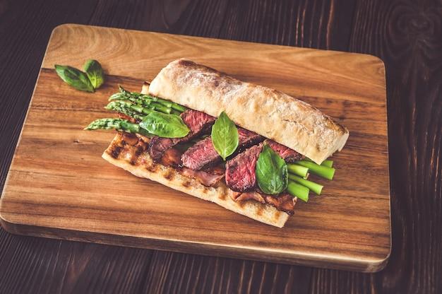 Sandwich mit spargel und rindersteakscheiben auf dem holzbrett