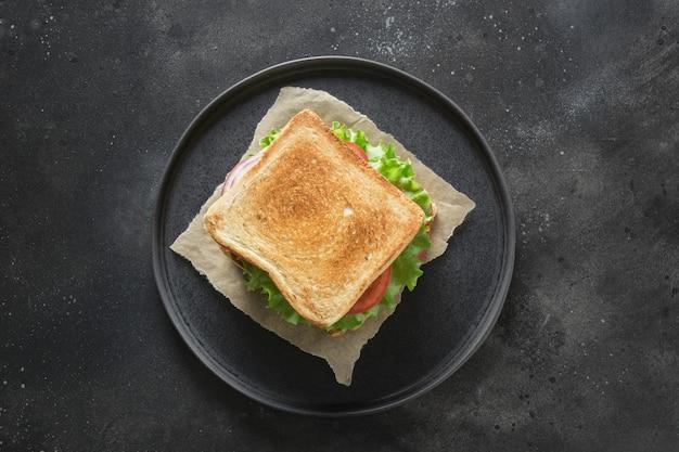 Sandwich mit speck, tomate, zwiebel, salat auf schwarzem hintergrund. isoliert. sicht von oben.