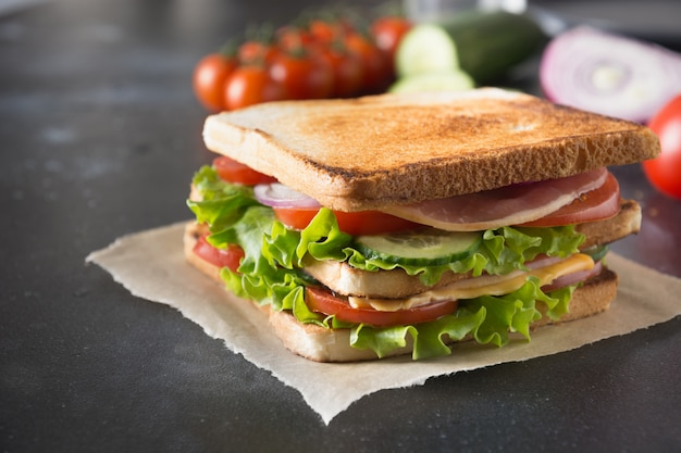 Sandwich mit speck, tomate, zwiebel, salat auf schwarzem. nahansicht.