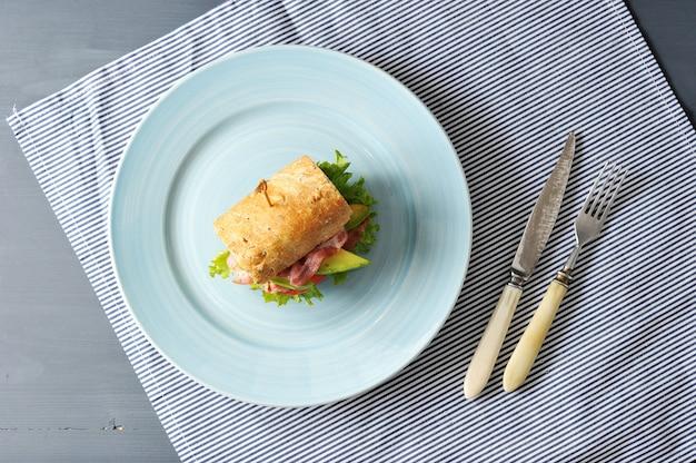 Sandwich mit speck und avocado mit einem spieß durchbohrt