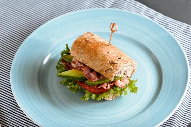 Sandwich mit speck und avocado mit spießen durchbohrt